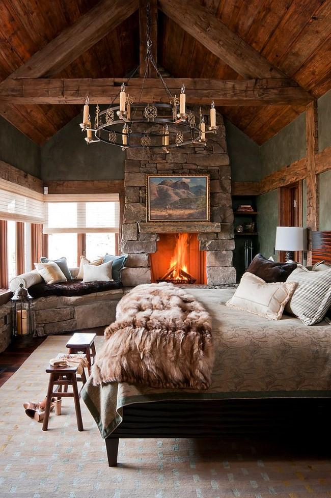 Каменный камин и зона отдыха уютной спальни в деревенском стиле.