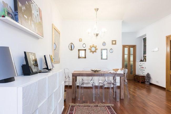 Стильные зеркала в серебристых и позолоченных рамах в интерьере столовой-гостиной.