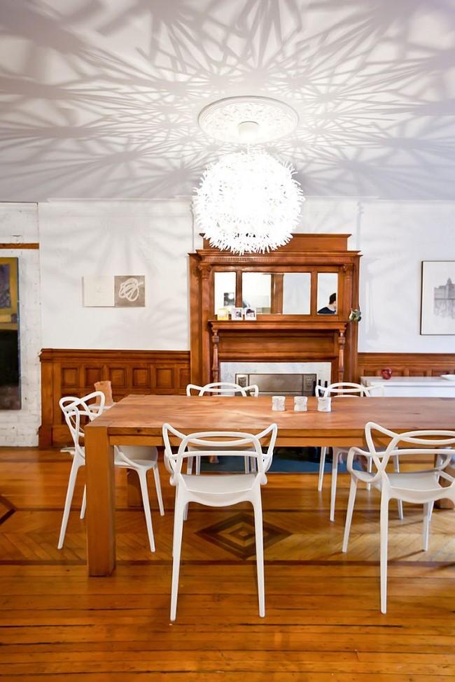 Стильная столовая в классическом стиле с оригинальной люстрой и деревянной мебелью.