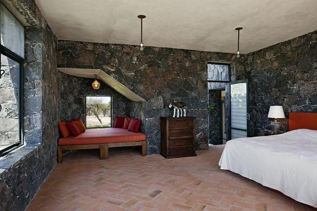 Уютная спальня в средиземноморском стиле с каменным стенами и керамической плиткой.
