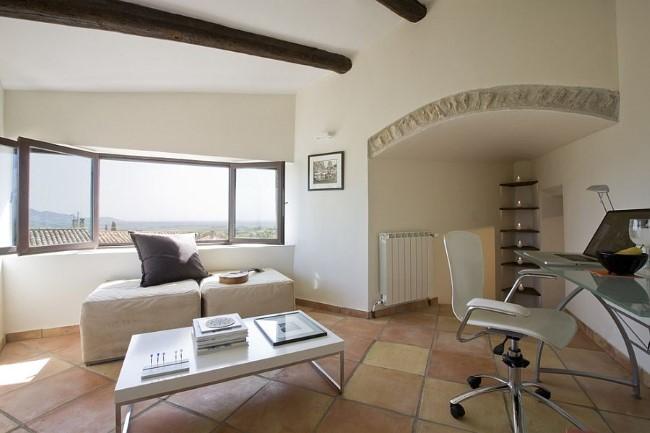 Средиземноморский домашний кабинет с уютной зоной отдыха и терракотовой плиткой.