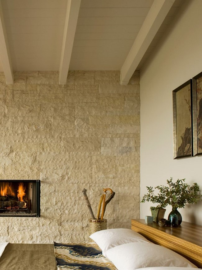 Уютная современная спальня с белой каменной стеной и камином.