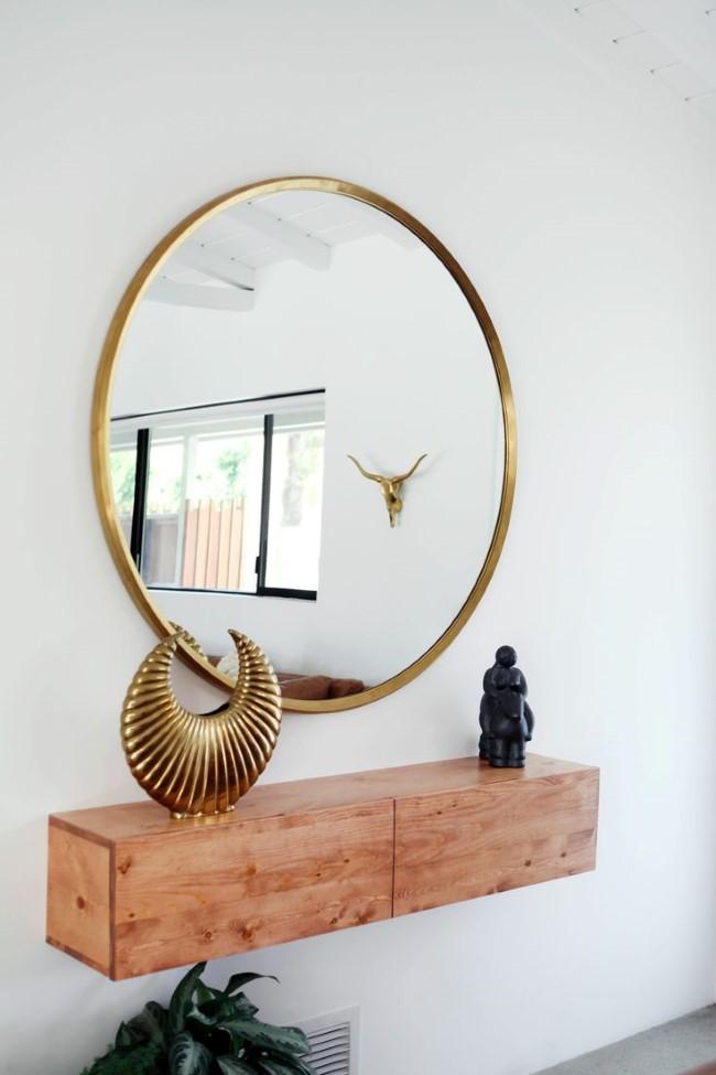 Стильное овальное зеркало в позолоченной раме в интерьере минималистической прихожей.