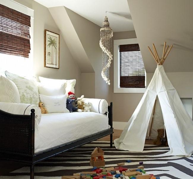 Детская палатка и раскладной уютный диван в стильной гостевой-игровой комнате.
