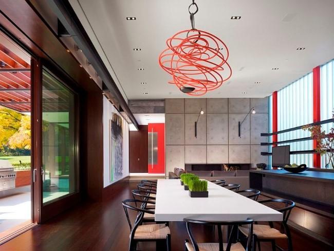 Красная подвесная люстра и люминесцентные светильники в интерьере просторной столовой-гостиной.