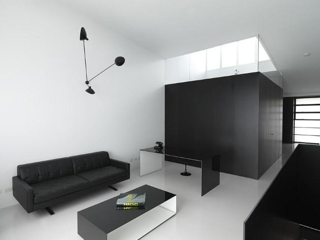 Минималистический современный домашний кабинет с белыми стенами и черной мебелью.