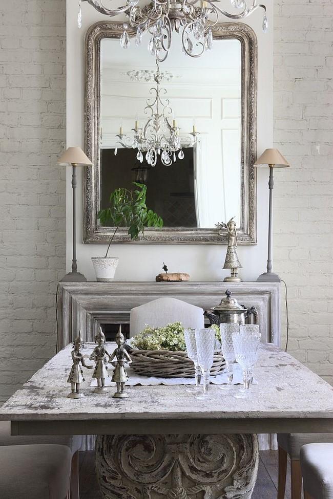 Большое зеркало в старинной раме и винтажная люстра в интерьере шебби шик столовой.
