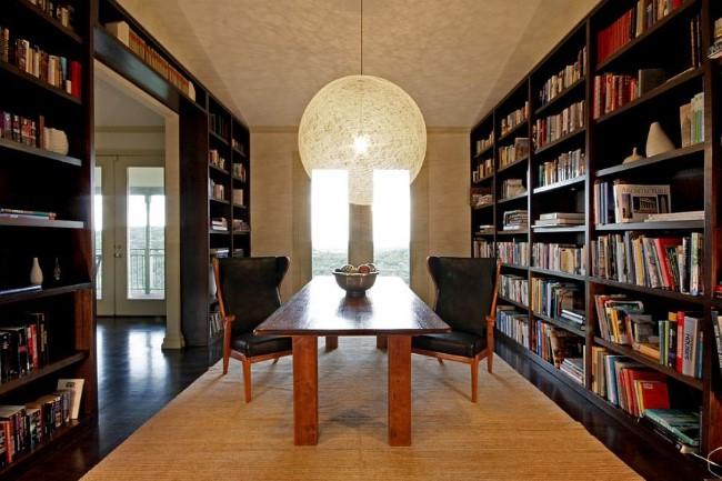Минималистическая столовая с массивными книжными шкафами вдоль стен и необычными светильниками.