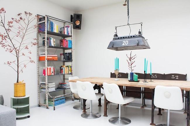 Театральный прожектор и индустриальный книжный стеллаж в современной столовой.