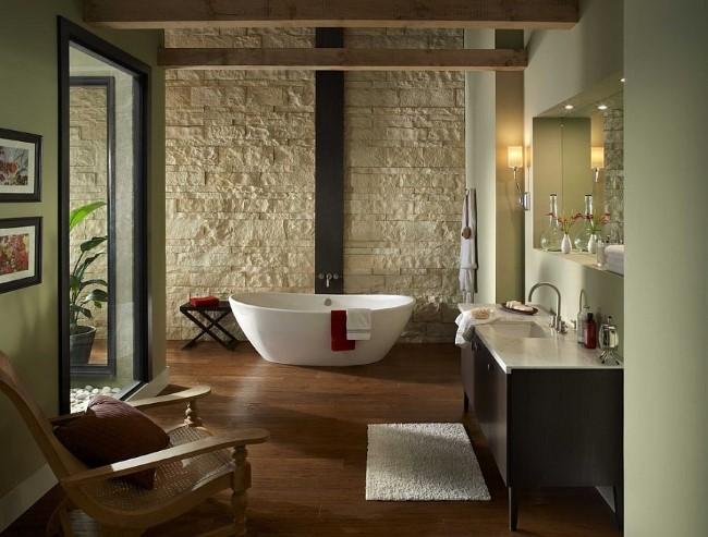 Каменные светлые стены и темно-коричневое дерево в просторной современной ванной.
