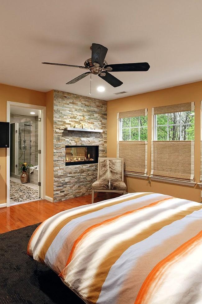 Каменная кладка и встроенный искусственный камин в современной спальне.