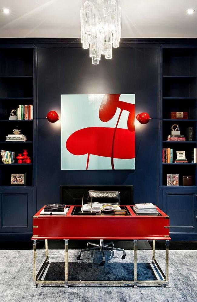 Красный письменный стол и картины в интерьере черно-белого домашнего кабинета.