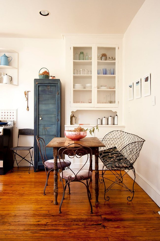 Маленький деревянный столик и кованая мебель в уютной столовой-кухне.