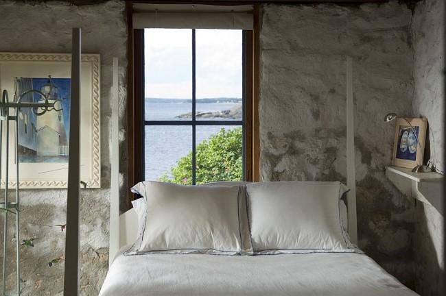 Стильные картины и каменная кладка в интерьере небольшой спальни с видом на океан.