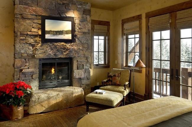 Каменная кладка и деревянные дубовые панели в интерьере маленькой деревенской спальни.