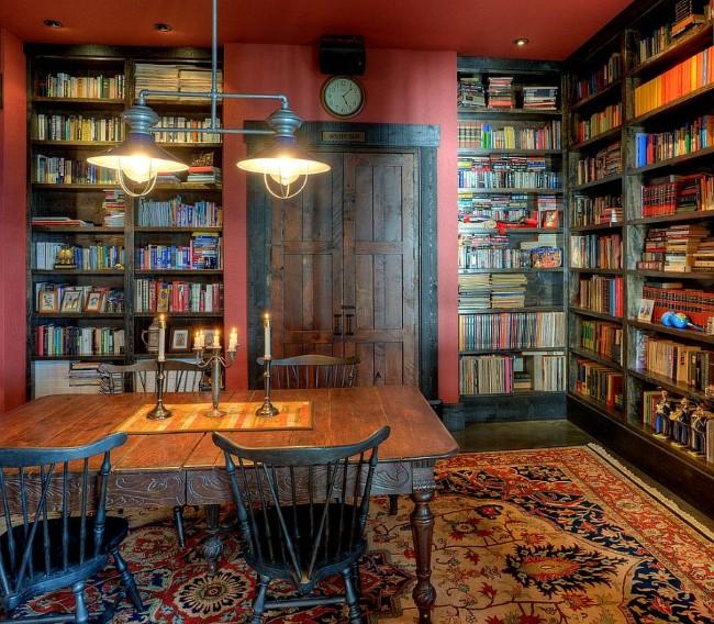 Стильная библиотека-домашний офис с красными стенами и мебелью в деревенском стиле.