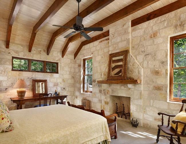 Белая каменная стена в интерьере небольшой деревенской спальни.