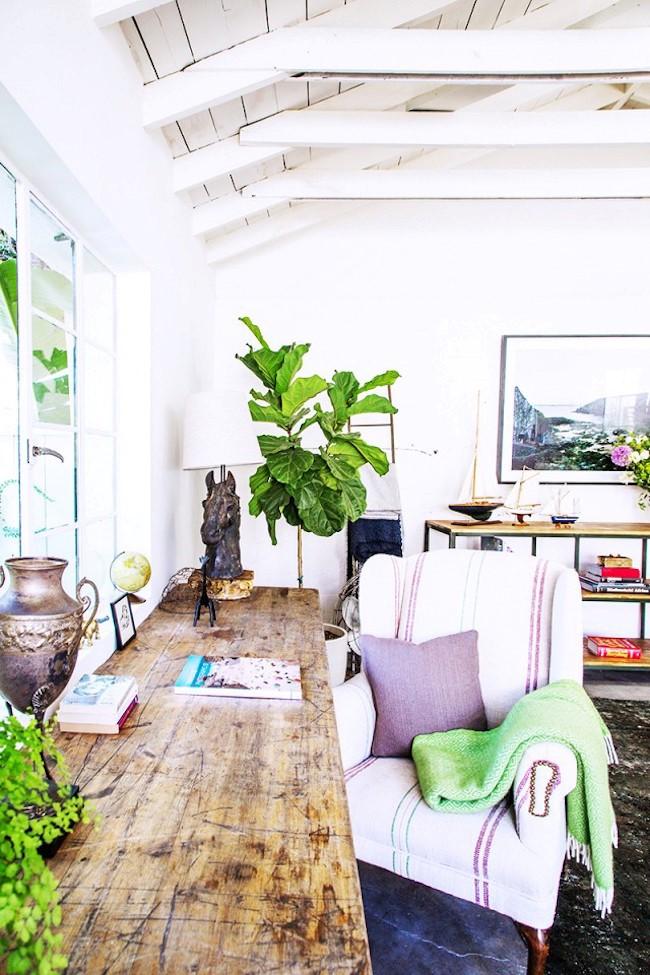 Просторная светлая комната в экостиле с живыми растениями и дубовым рабочим столом.