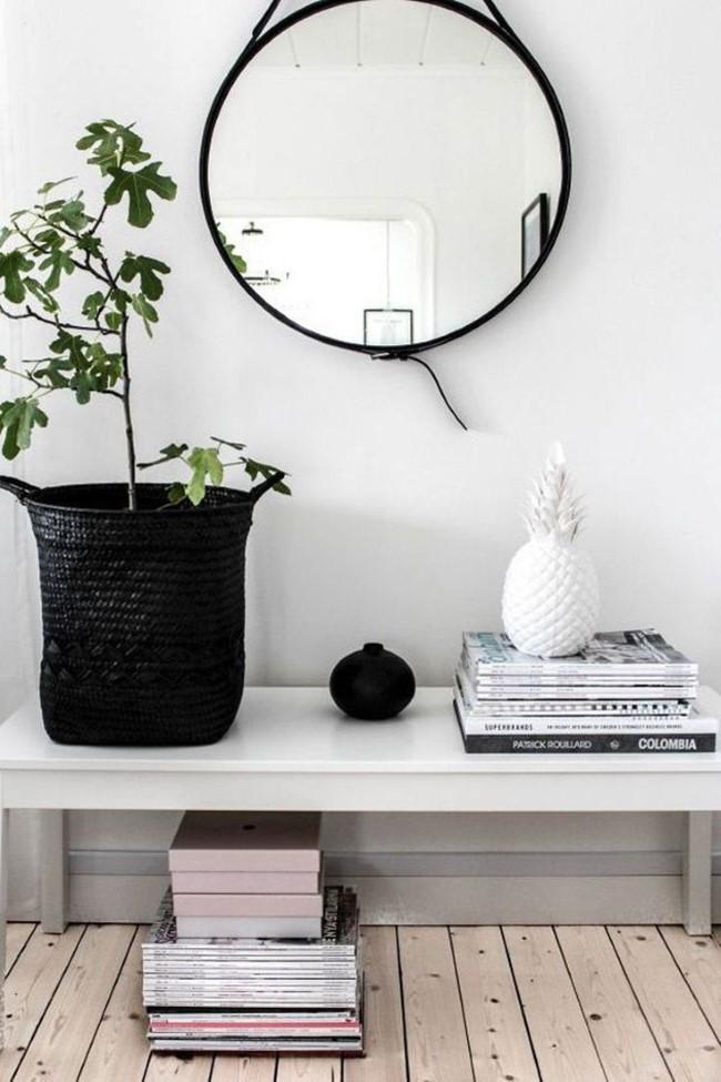 Скандинавская стильная прихожая с круглым зеркалом и черно-белыми аксессуарами.