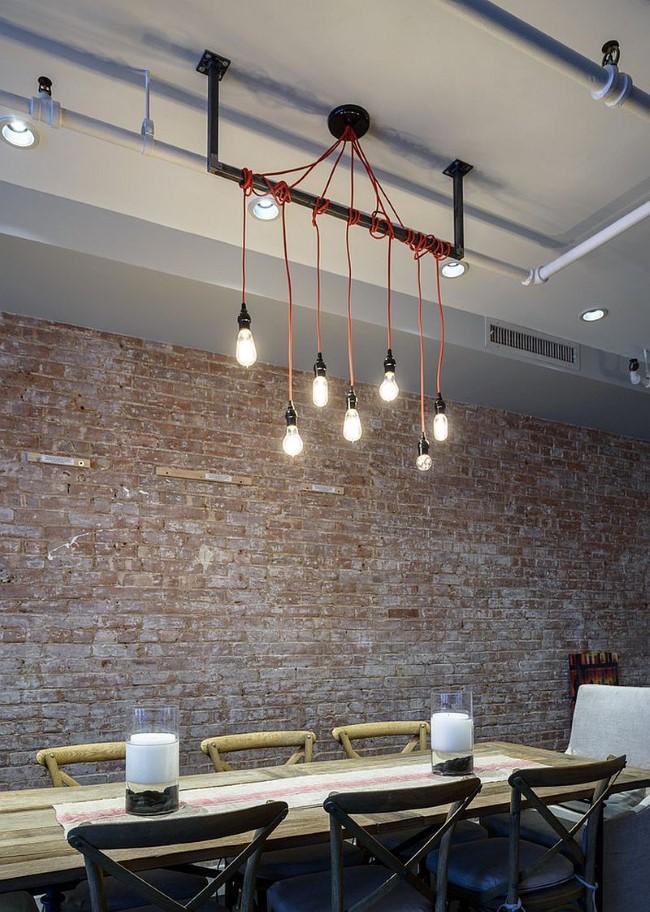 Индустриальная столовая с каменными стенами и минималистическими светильниками.