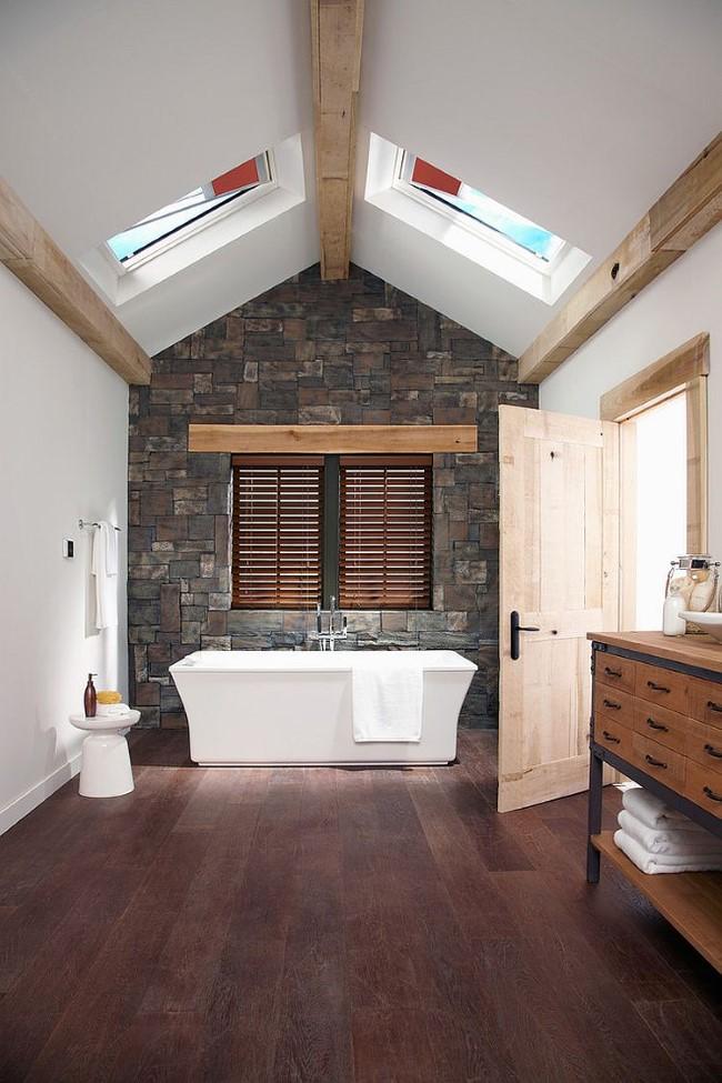 Каменная кладка стен и деревянное напольное покрытие в интерьере современной ванной комнаты.