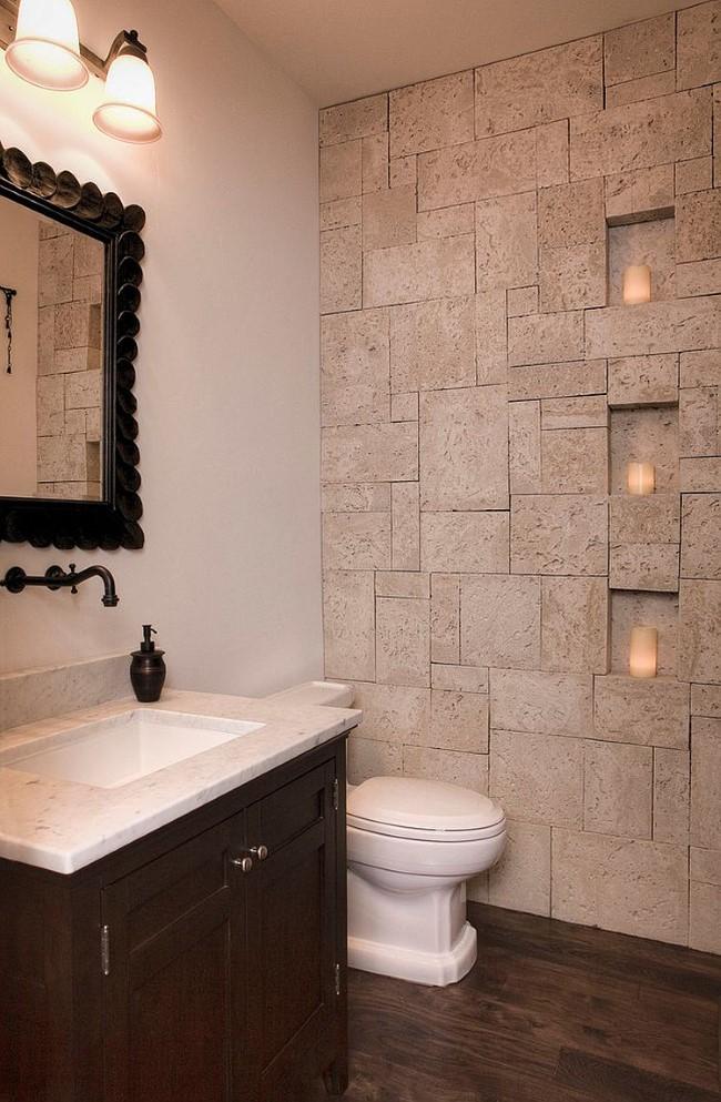 Матовая каменная стена с нишами для светильников в интерьере современной ванной.