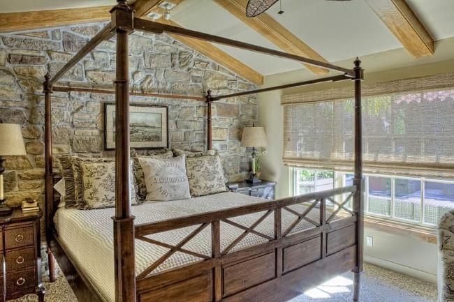 Каменная кладка и массивная дубовая кровать в интерьере стильной спальни.
