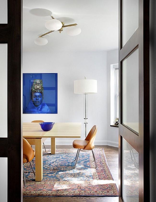 Уютная светлая столовая с мягким ковровым покрытием под обеденным столом.
