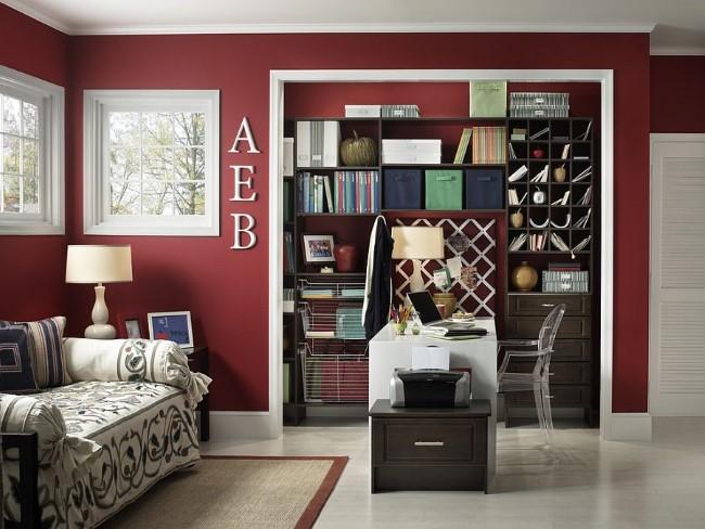 Уютный домашний кабинет с красно-белыми стенами и встроенным книжным шкафом.