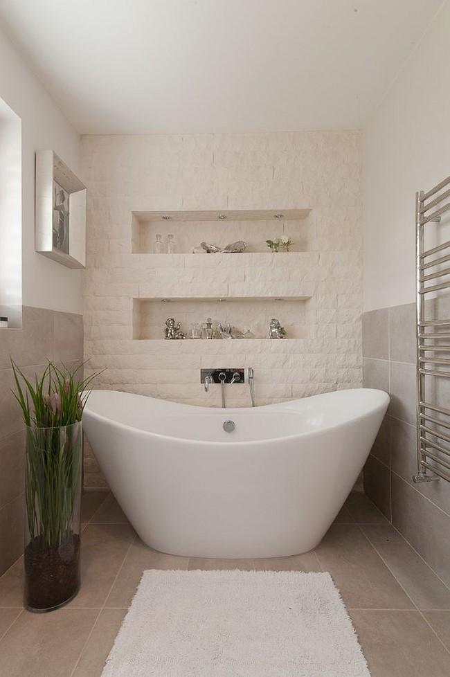 Белая каменная кладка и светло-серая плитка в интерьере маленькой ванной комнаты.