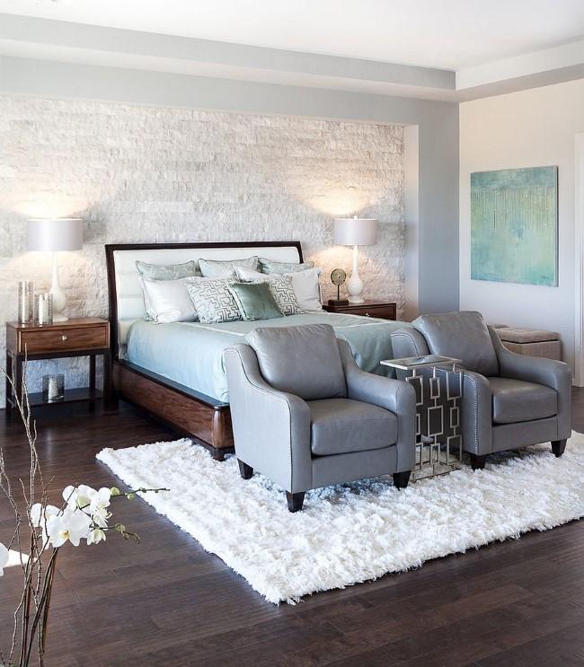 Белая кирпичная стена, натуральное дерево и живые цветы в современной светлой спальне.