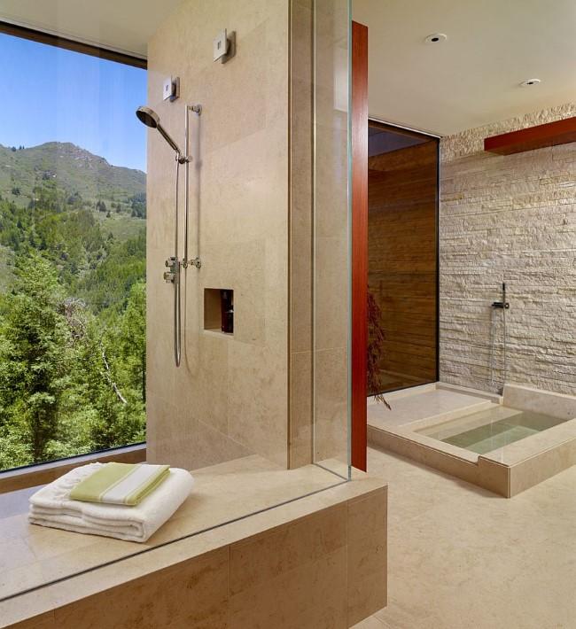 Стильная ванная комната с каменными стенами и большими окнами с видом на лес.