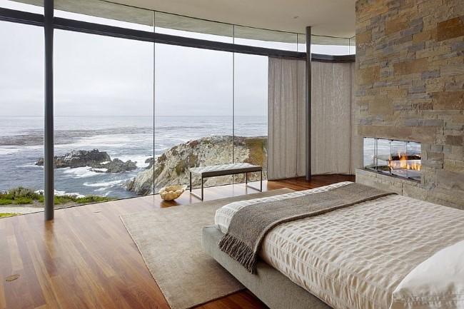 Стеклянные стены и выложенный камнем камин в интерьере просторной спальни.