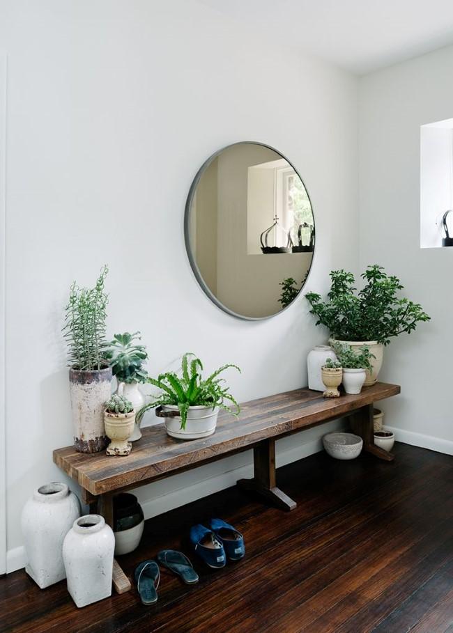 Овальное зеркало и комнатные растения в интерьере скандинавской прихожей.