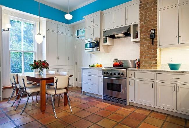 Эклектическая кухня-столовая с каменной кладкой, белой мебелью и терракотовой плиткой.