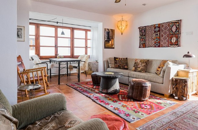 Необычная экзотическая гостиная с мягкой мебелью, узорчатыми подушками и кожаными пуфами.