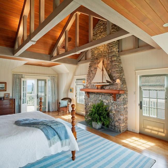 Бело-голубая спальня в морском стиле с каменной стеной и деревянными панелями.