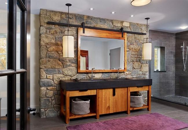 Стильная ванная комната со светло-коричневой деревянной мебелью и каменными стенами.