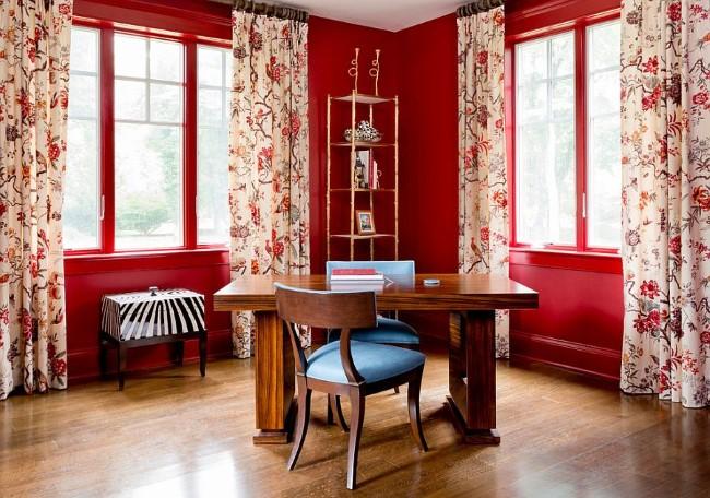 Красные стены и узорчатые портьеры с красным рисунком в интерьере домашнего кабинета.