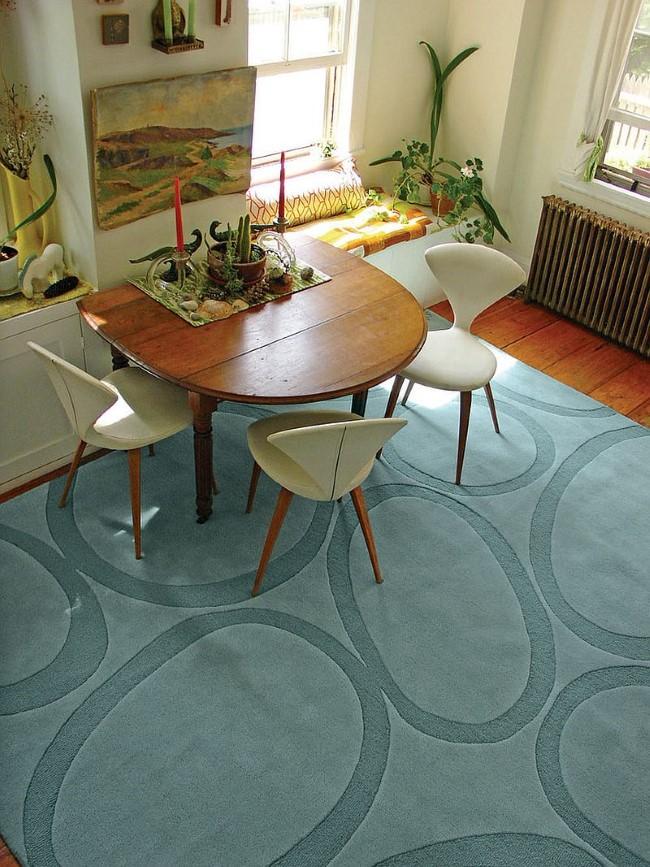 Прямоугольной светло-синий ковер в интерьере средиземноморской гостиной-столовой.
