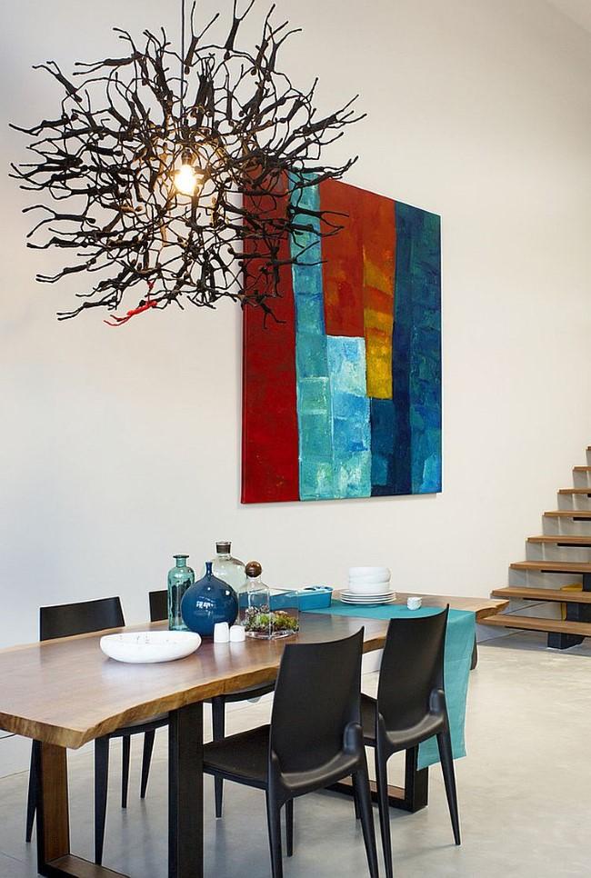 Белая столовая с деревянной мебелью и вычурными абстрактными люстрами.