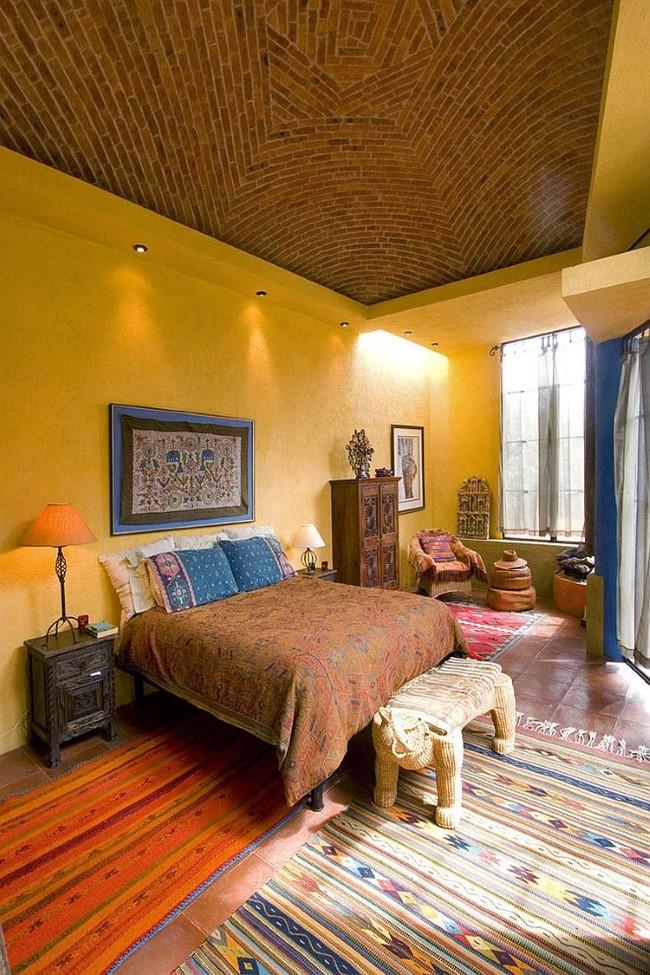 Терракотовая плитка и напольные узорчатые покрытия на полу экзотической спальни.