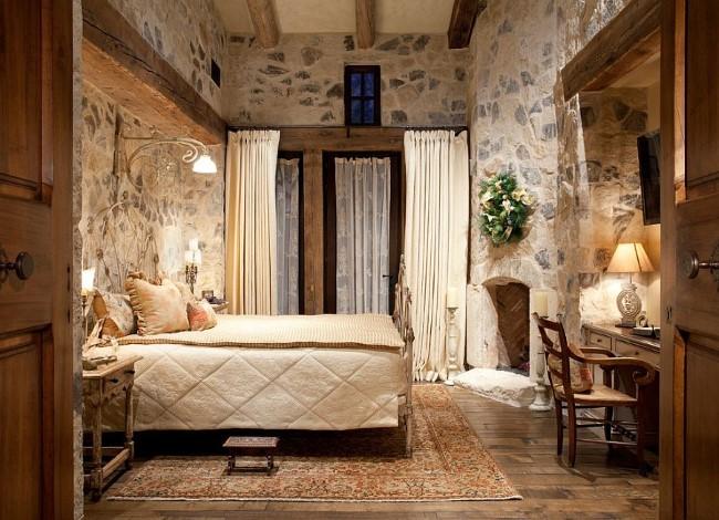 Небольшая уютная спальня с деревянной мебелью и каменными стенами.