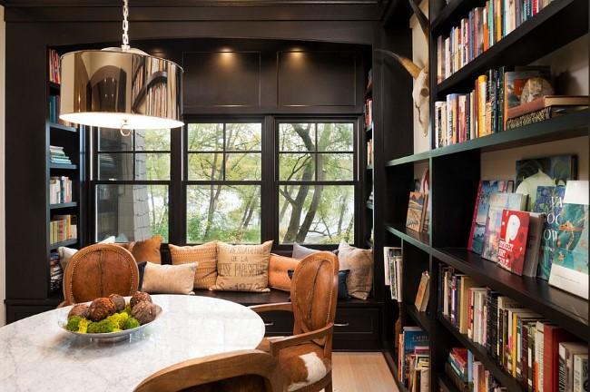 Маленькая столовая в темных тонах с книжным шкафом и уютной зоной для чтения.