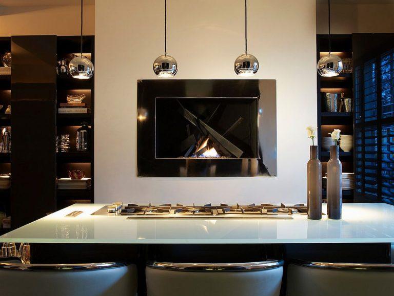 Аккуратный и завораживающий современный камин становится центром в потрясающей современной кухне.
